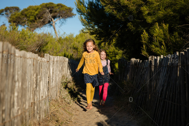 Two little girls running on path between wooden fences
