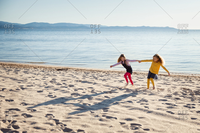 Sisters playing together on a sandy beach