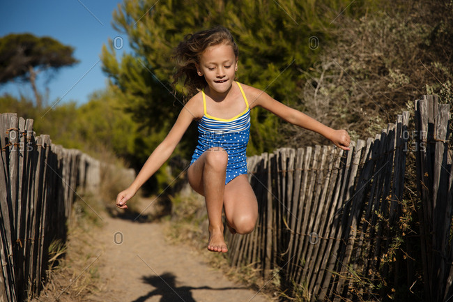 Blonde girl running and leaping on sandy path