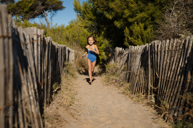 Blonde girl running on sandy path between wooden fences