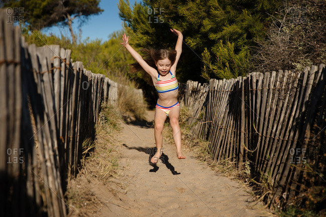Little girl running and jumping on a sandy path