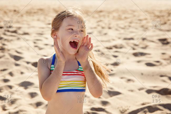 Little girl on a beach yelling