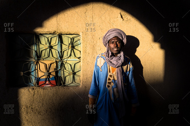 MOROCCO - AUGUST 15, 2017: Black man wearing traditional clothes and turban standing at wall and looking at camera