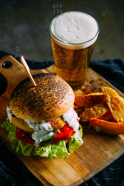 Deluxe vegetarian burger made with chickpeas, with fries and a glass of beer