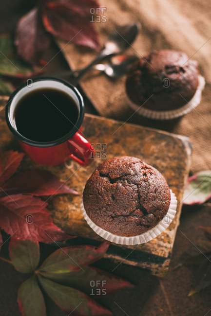 Chocolate muffin with coffee cup with leaves on dark background