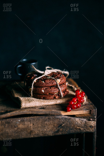 Brownie cookies in dark wooden background with red currants