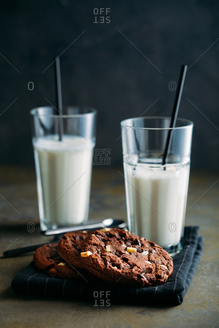 Chocolate cookies and glasses of milk on dark background