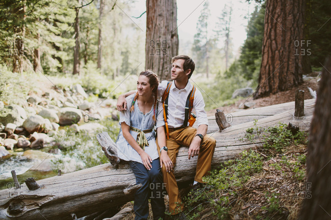 Couple sitting on tree log in the woods