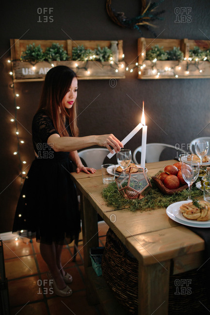 Woman lighting dinner candles