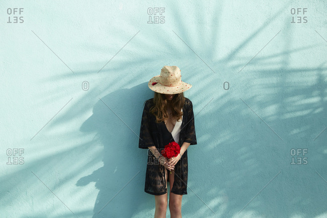 Woman wears straw hat and swimwear