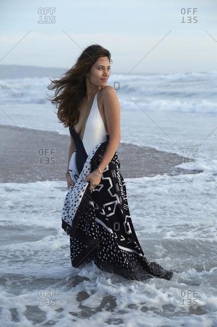 Woman in swimwear stands in surf