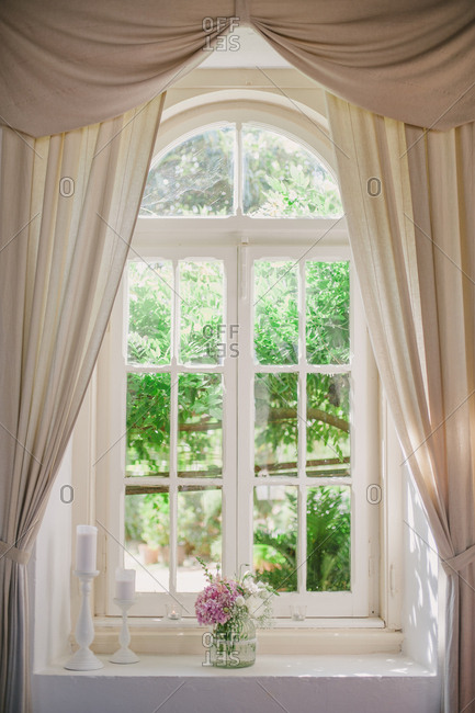 Curtains around curved window with vase of flowers and candles on windowsill