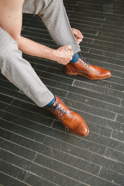 Person tying brown dress shoes