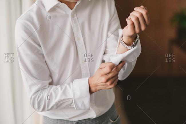 Man adjusting sleeve on dress shirt