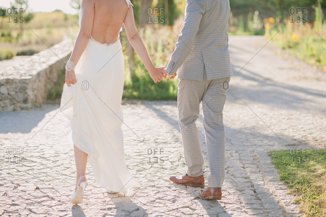 Back view of bride and groom holding hands while walking on stone path outside