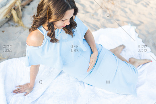 Pregnant woman lounging on beach