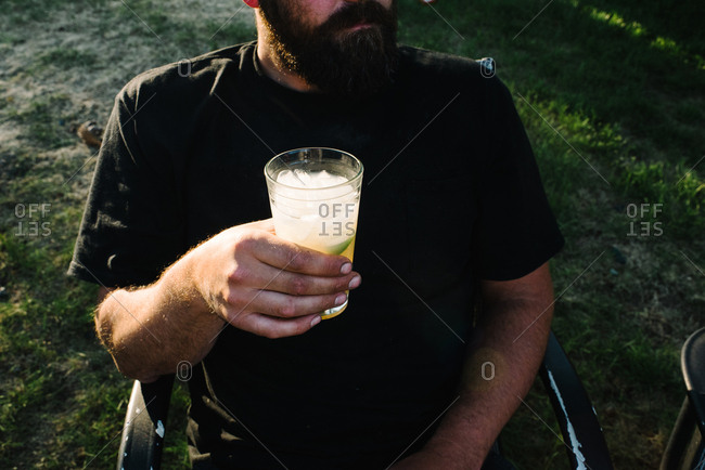 Man having drink sitting outside