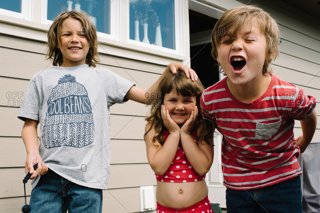 Three kids being silly outside home