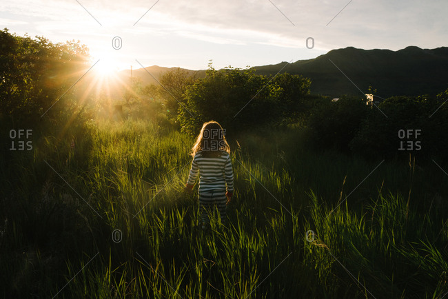 Girl in pajamas in sunlight in field