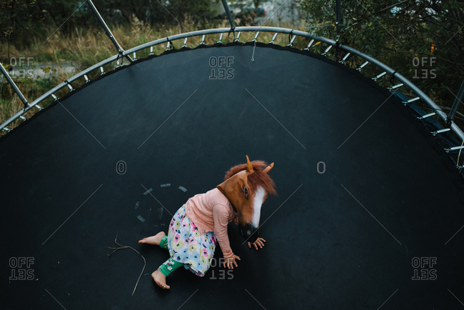 Girl on trampoline in horse mask