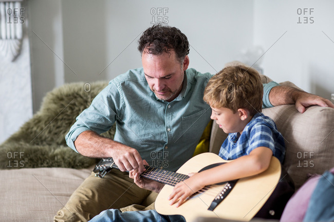 Father teaching son guitar chords stock photo - OFFSET