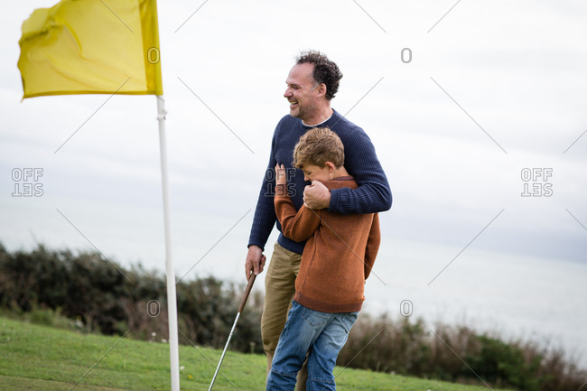 Father hugging son on golf course
