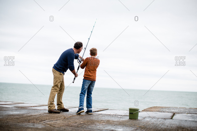 Father helping son fish