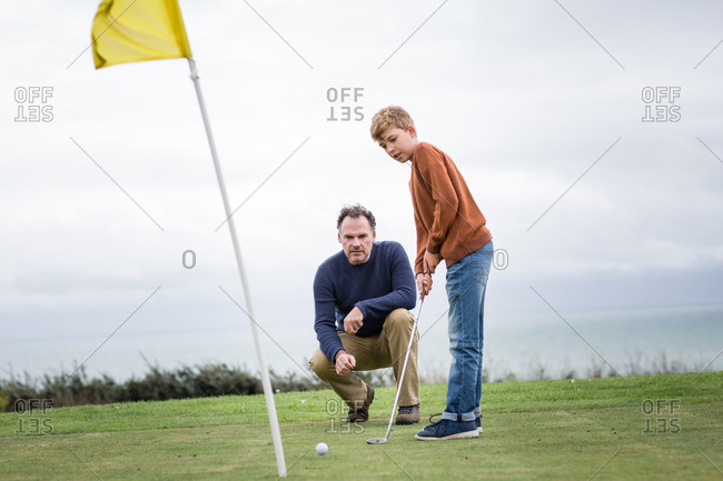 Father watching son play golf