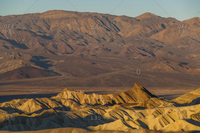 Sunrise shows Manly Beacon sandstone rock formation at Zabriskie Point in Death Valley National Park in California