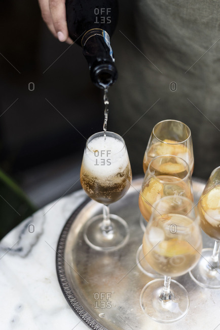 Person pouring spritz cocktail with orange