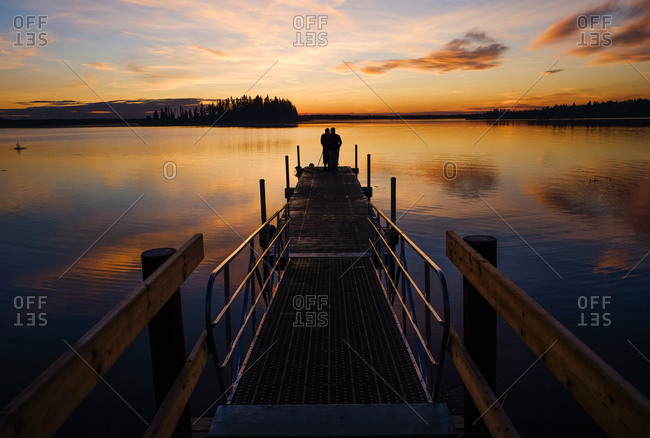 Silhouette of two people standing on a dock at sunset overlooking lake