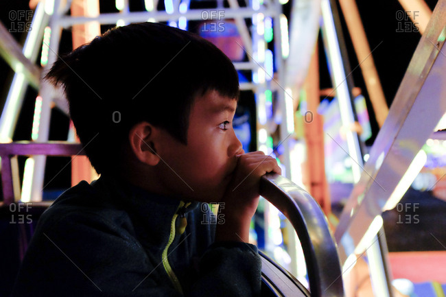 Boy looking out of cart on a big wheel