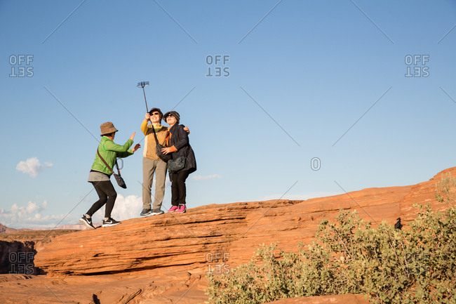 Page, Arizona, USA - September 14, 2017: Women together on rock taking a selfie with a selfie stick at Horseshoe Bend