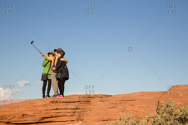 Page, Arizona, USA - September 14, 2017: Three women standing on rock taking a selfie with a selfie stick at Horseshoe Bend
