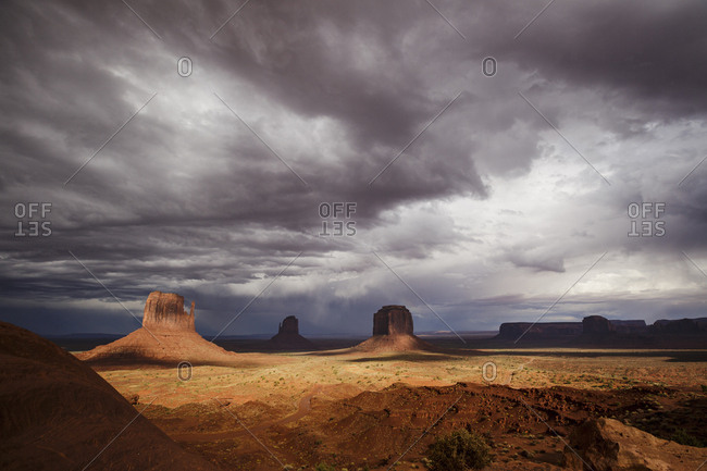 Scenic view of Monument Valley with dark clouds