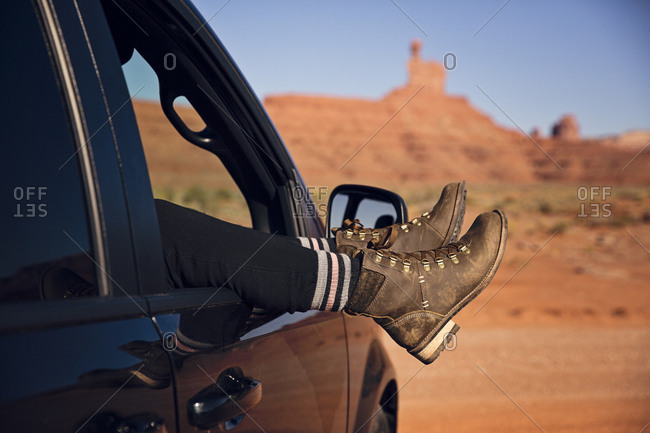 Women relaxing with her legs out car window on road trip