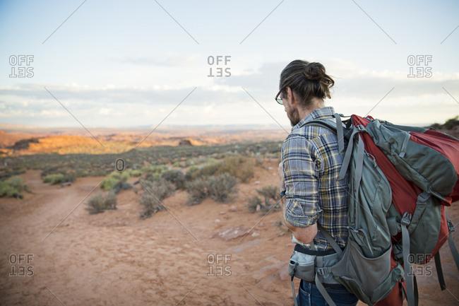 Man hiking a red dirt trail