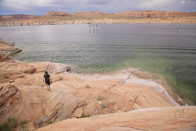 Man walking along the shore of Lake Powell