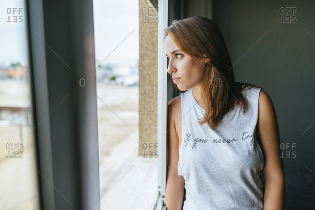 Portrait of woman looking out of the window of her house