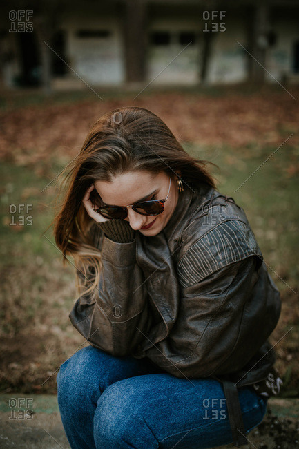 Beautiful woman wearing leather jacket looking down.