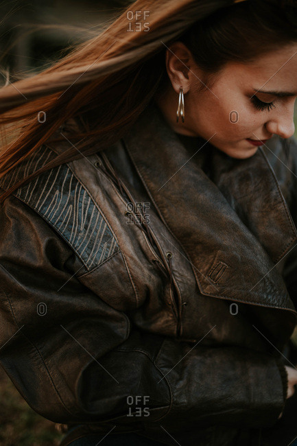 Vertical shot of beautiful woman wearing leather jacket looking down.