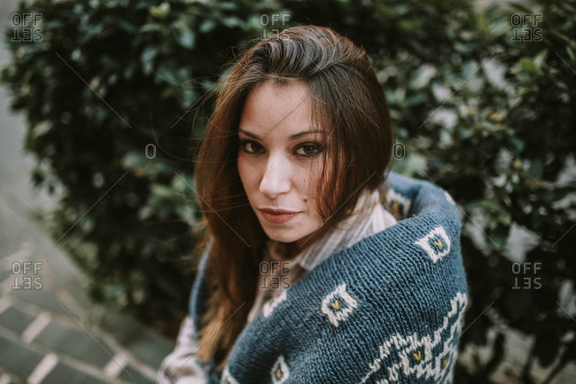 Horizontal outdoors portrait of young female wearing warm sweater and looking at camera.