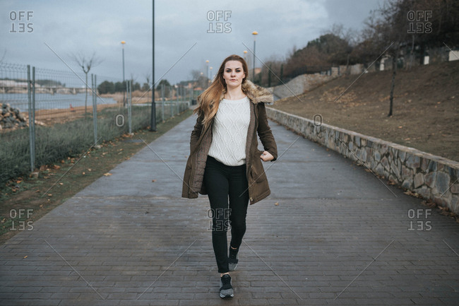 Young serious woman on the walkway. Horizontal outdoors shot.