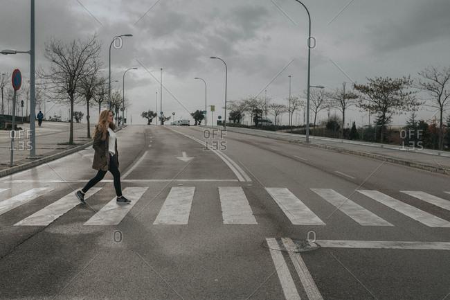Side view of female walking on a crosswalk in cloudy day.