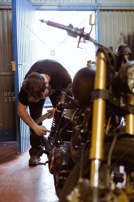 Man doing motorcycle maintenance in garage. Vertical indoors shot.