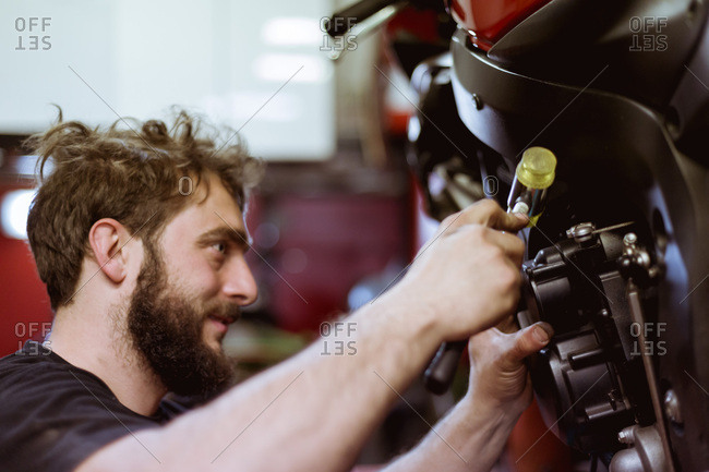 Side view of worker doing maintenance of motorcycle in garage.