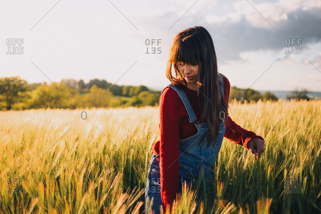 Young woman in denim walking in field in the evening.