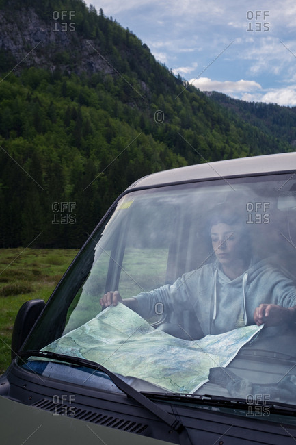 Tourist woman sitting in car in mountains and reading map.