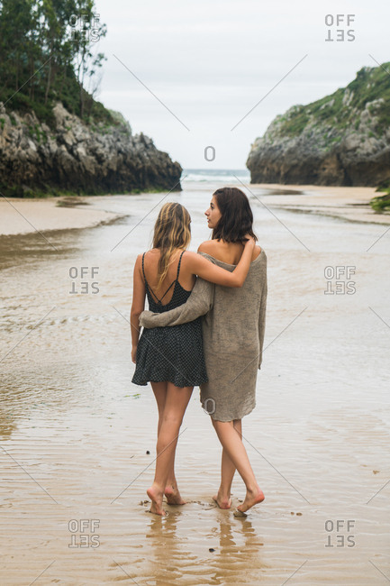 Girls hugging walking on the shore