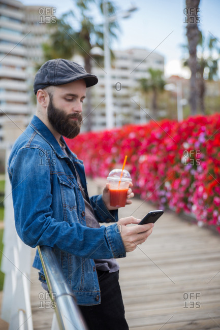 Young bearded man leaning on a handrail having a smoothie and browsing the smartphone